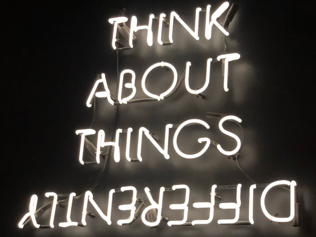 Neon lights spelling - Think about things differently.